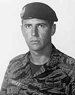 Portrait of a Marine. He is wearing a black beret and tiger stripe camouflage. His name tape says Ripley.