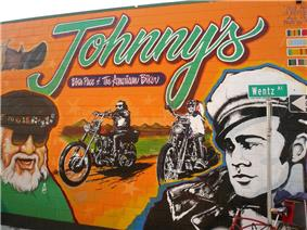 Wall of a building with mural of a bearded man with sunglasses wearing a beret, a young man in a white hat in front of two riders on chopper motorcycles below the legend Johnny's the birthplace of the American biker.