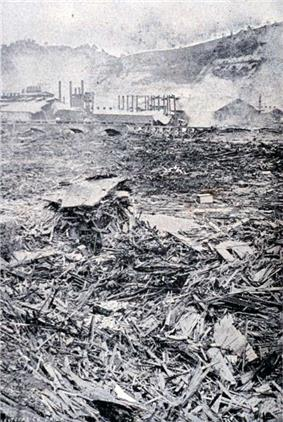 Debris litters and completely covers the ground above a Pennsylvania Railroad bridge. A small bridge and several mills and smokestacks are viewable in the distance.