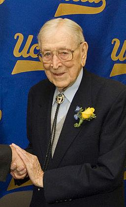 A smiling, elderly man is shown from the waist up. He is shaking someone's hand, but that person is out of the picture. The man is wearing a dark suit with a yellow boutonniere. He has thin white hair and large glasses. He is standing in front of a blue screen that has the script
