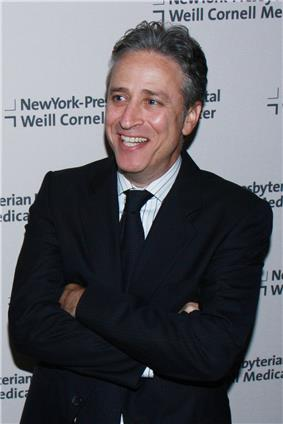 Photo of a Jewish male smiling while looking toward his right side and crossing his arms. He is wearing a black coat over a white shirt and a black tie.