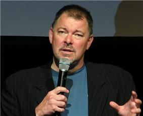 Bearded man in a black jacket gesturing while talking into a microphone.