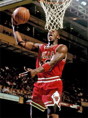 A basketball player, wearing a red jersey, is holding a basketball.