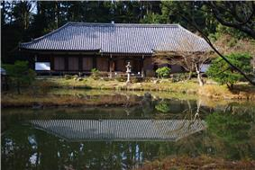 Low and wide building with hipped roof, white walls, beyond a lake.