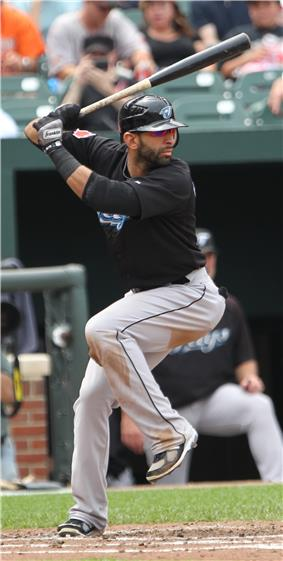A man in a black batting helmet, black baseball jersey, and grey pants holds a baseball bat midway into right-handed swing with his left leg up in the air.