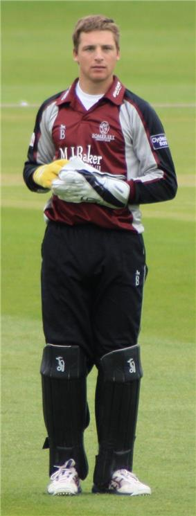 A young man with light brown hair is standing on some grass. He is wearing a burgundy, grey and black cricket uniform, large gloves and black trousers covered by black think pads on his lower legs.