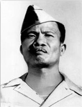 Head of a man with dark hair and a defiant look on his face, wearing a garrison cap tilted over one ear and a shirt with a wide, flat collar.