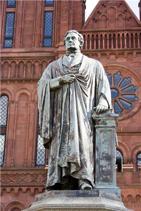 An aged bronze statue of a man wearing a robe. His left hand rests on a book which sits on a pedestal and the statue is in front of a red brick building reminiscent of a Romanesque Cathedral