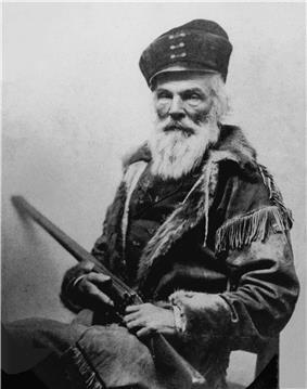 Elderly man with bear and hat holding a long barrel gun