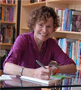Blume smiling while signing a book