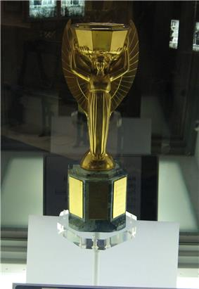 Golden trophy in a presentation case. It depicts the Greek goddess Nike standing with arms aloft.