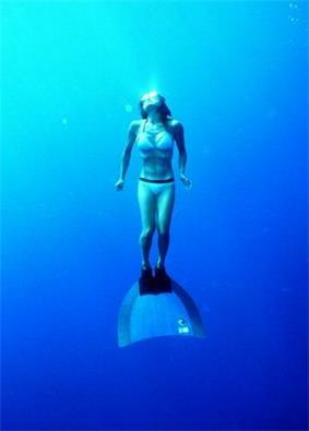Woman freediving with a monofin