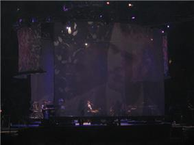 A stage with a big screen display showing a man with a beard. Sitting in a piano, a man with long curly hair wears a white shirt, with the sleeves roll back, and a black vest, plays the piano. To the man's left, a man can be seen standing playing an electric piano.