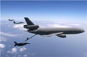 Large three-engined aircraft refueling a jet fighter while two more of the latter fly in the distance.