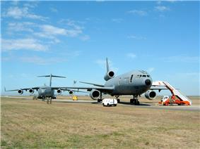 Two large gray jet aircraft on roomy ramp surrounded by grass, both angled away from the runway. The one closer to camera is three-engined, while the one further in the background is fourengined.