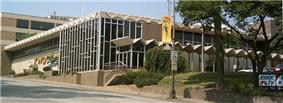 A large TV station building. The building has many windows and a large awning runs parallel to one side. A small sign out front and a large sign on the side of the building both say KWQC TV 6
