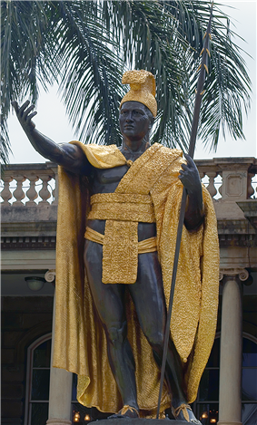An impressive statue of a dark-skinned man, richly dressed in native garb.  One arm is extended, as if in greeting, and he holds a spear, butt end grounded, in the other.