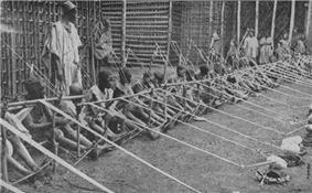 A row of more than a dozen children holding wooden looms stretches into the distance.