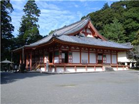 Wooden building with raised floor, white walls, vermillion red beams, an open veranda and a hip-and-gable roof.