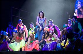 Kareena Kapoor performing dance on a stage, alongside a group of performers