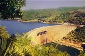 An impressive dam, built in a semi-circular shape, viewed from a vantage point above and to the right of its front. A large lake can be seen on the other side of the dam as well as a river before it.