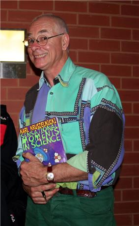 Karl Kruszelnicki holding a copy of his book Sensational Moments in Science