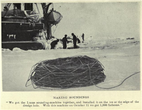 In the foreground, standing on sea ice, is a massive coil of rope or steel wire. In the background three men stand by a hole in the ice. Part of a ship's hull is visible, left background.