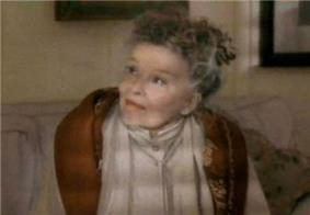 Screenshot of Hepburn, now an elderly woman, seated on a sofa