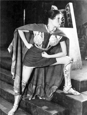 Hepburn, a young woman, dressed in a short tunic and armour, acting in a play.