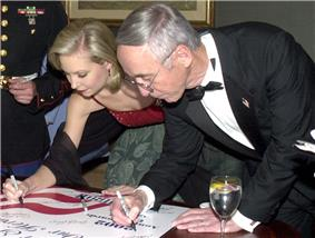 A young woman and an older man, both dressed in formal wear, leaning over to sign a poster.