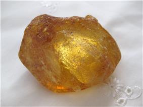 A dark gold transparent rough lump of resin
