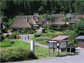 Wooden houses with thatched roofs in a mountain setting.