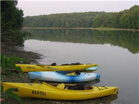 One blue and two yellow kayaks on the shore of a lake, which reflects surrounding pine trees