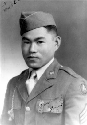 Head and shoulders of a young man wearing a garrison cap and a military jacket with three chevrons on the upper left sleeve and a whistle hanging from a chain attached to his right shoulder. In the top left corner of the photo is written