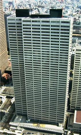 Aerial view of a white, rectangular high-rise lined with rows of windows
