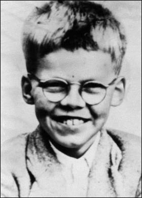 Head and shoulders monochrome photograph of a smiling short-haired young boy wearing spectacles.