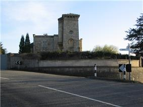 Stone building with tower to right hand side. In front is a wall separating the building from the road.