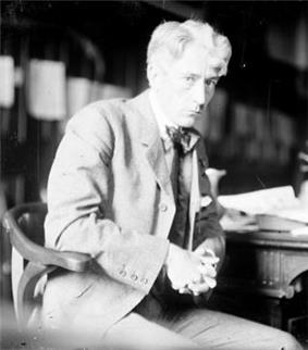 A man in a tweed suit and bowtie sits in a wooden chair beside a desk. He is leaning on the desk and faces to the right but gazes into the camera out of the corner of his eye. His wavy hair is parted, while his hands are folded above his lap.