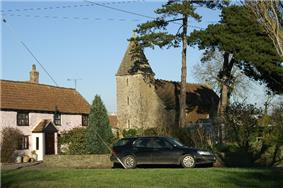 Stone church with square tower in the background partially obscured by trees. To the left is a pink painted house with red roof and in the foreground a car and grass area.