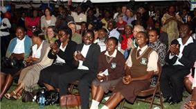 Audience seated in rows, smiling and clapping