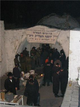 A colour photograph showing a cluster of black-garbed men in hats, along with a cluster of uniformed soldiers, standing under a whitewashed, arched opening with a doorway behind and a low dome dimly visible in the background