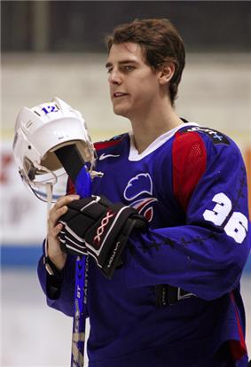 An ice hockey player standing, holding is ice hockey stick with his helmet rested on the top. He has short brown hair and is wearing a blue uniform.
