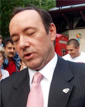 A close-up image of a man sporting a black suit and pink tie.