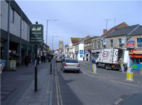Street scene showing shops on left and right, with cars and vans on road. On the left hand pavement is a sign saying welcome to Keynsham high street.