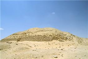 Ruined pyramid raising a few metres from the desert floor, a heap of sand and mudbricks.
