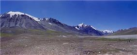 Some tall, bluegrey mountains rise out of brown soil below a deep blue sky