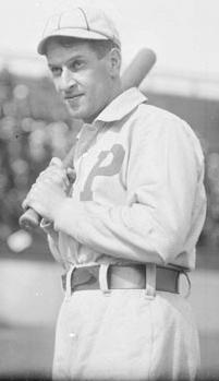 A black-and-white photograph of a man in a white baseball uniform with the letter