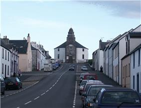 A wide street leads up a slope with parked cares and stone houses painted in whites and yellows on either side. At the end of the street there is a grey and white building with a short spire.