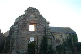 Stone wall with window of ruined building.