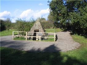 A pyramidal stone structure stands in a small clearing surrounded by small trees and bushes. The structure, enclosed by a fence, has an opening in the front.